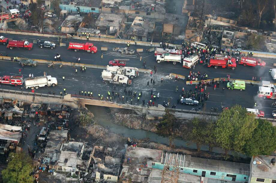 Aerial view shows first responders working next to destroyed homes and vehicles after a gas tanker truck exploded on a highway in the Mexico City suburb of Ecatepec early Tuesday, May 7, 2013.  The blast killed and injured dozens, according to the Citizen Safety Department of Mexico State. Officials did not rule out the possibility the death toll could rise more as emergency workers continued sifting through the charred remains of vehicles and homes built near the highway on the northern edge of the metropolis. Photo: AP