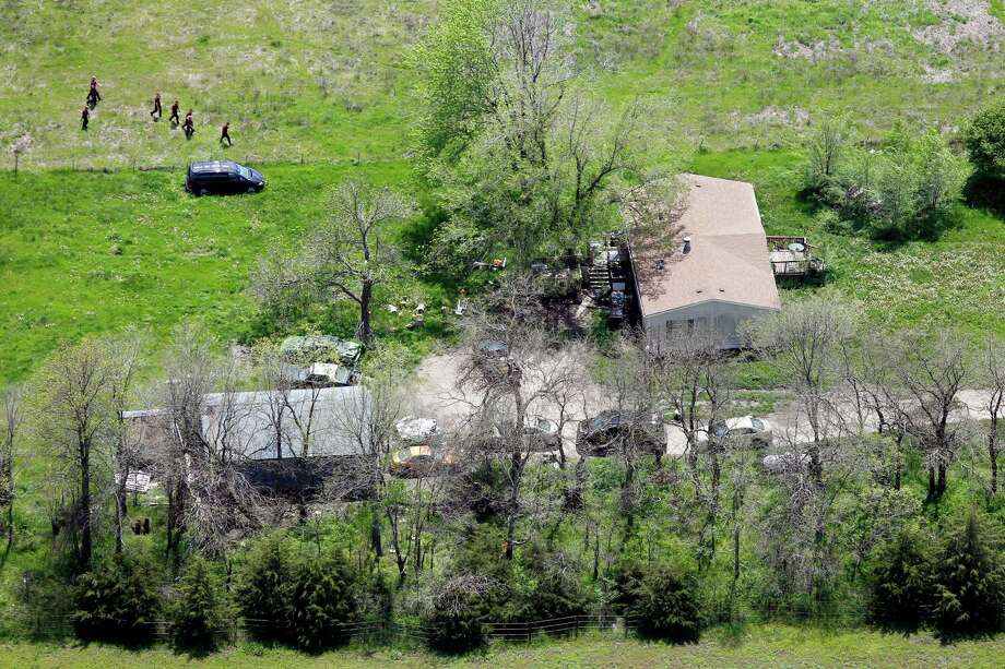 In this May 9, 2013, photo searchers comb the property around a farmhouse near Ottawa, Kan., for 18-month-old Lana Bailey who is missing. Crews resumed their search Friday for the girl who is presumed dead after the bodies of her mother, Kaylie Bailey, and two men were found at an eastern Kansas farm. Photo: AP