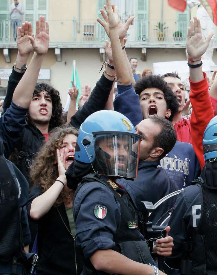 "Protesters shout during a Silvio Berlusconi's rally in Brescia, Italy, Saturday, May 11, 2013. Thousands of supporters of former Premier Silvio Berlusconi rallied in a northern Italian city Saturday to protest the media mogul's recent conviction by a Milan appeals court for tax fraud, cheering their hero as police in riot gear separated them from jeering opponents. The backers turned out for the ""Everyone for Silvio"" rally in a square outside the cathedral in Brescia, a small industrial city that is a bastion of the conservative leader's political support. As some arrived, waving pro-Berlusconi banners, some detractors shouted ""jail, jail."" Helmeted police holding plastic body shields moved in between the noisy camps to prevent any physical violence. Photo: AP"