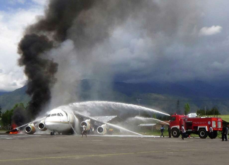 Fire fighters try to extinguish fire on a British-made BAe 146 cargo plane that caught fire while being unloaded at the airport in Wamena, Papua province, Indonesia, Wednesday, May 8, 2013. An official said that the plane caught fire after a drum of oil fell from the aircraft and somehow sparked the fire. Photo: AP