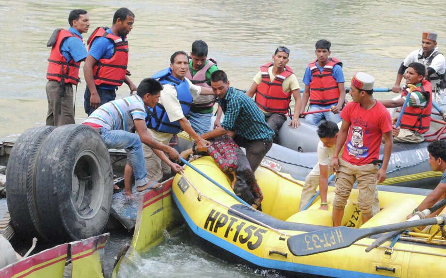 Rescue workers retrieve the lifeless body of a victim after a bus plunged into the Beas River near Kullu, India, Wednesday, May 8, 2013.  More than 30 people were killed when an overloaded bus plunged into the river from the Kullu-Mandi national highway Wednesday, according to a news agency. Photo: AP