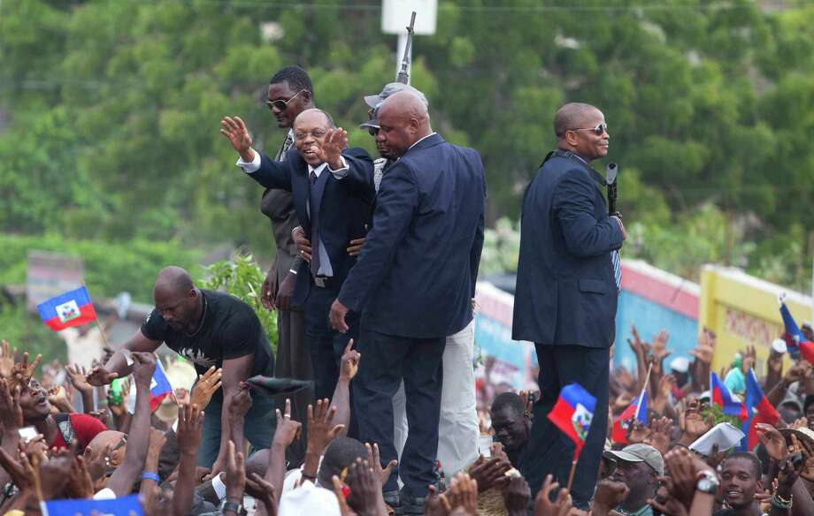 Flanked by body guards, former Haitian President Jean-Bertrand Aristide greets supporters as leaves the courthouse in Port-au-Prince, Haiti, Wednesday, May 8, 2013. Aristide greeted a small group of onlookers after testifying before a judge investigating the slaying of one of the country's most prominent journalists. The judge is questioning Aristide about the killing in April 2000 of Jean Dominique, a friend of the former president. Photo: AP