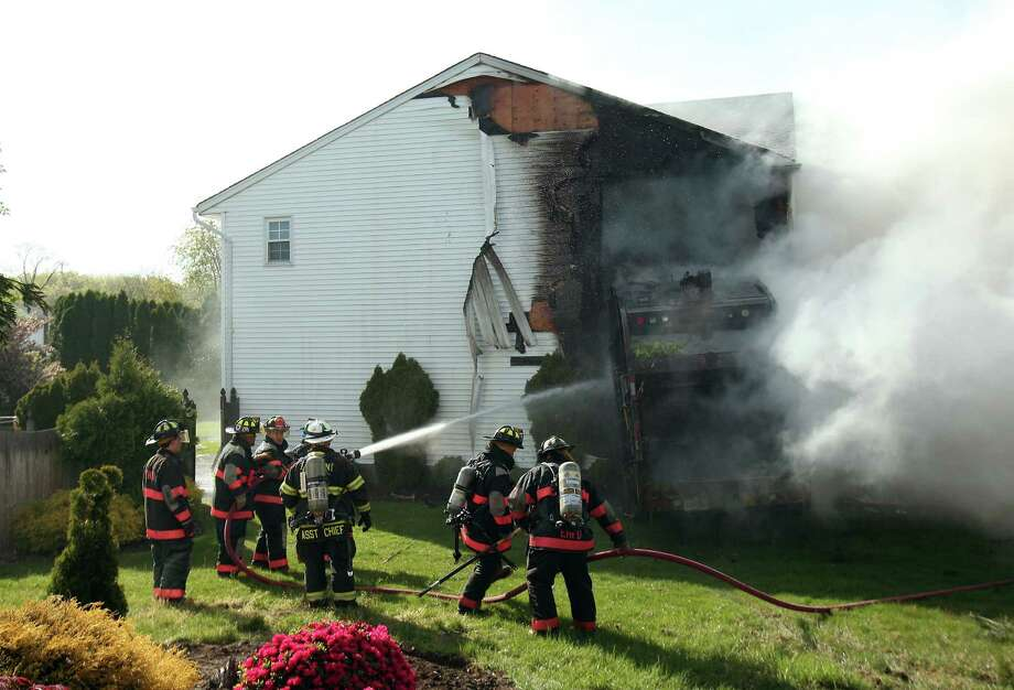 Firefighters and police work the scene were a  garbage truck struck a house, igniting a blaze within the home on Tuesday, May 7, 2013 in East Hanover, N.J.  (AP Photo/The Daily Record,  Bob Karp) Photo: AP