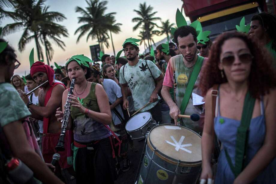 People play instruments as they participate in a legalization of marijuana march at Ipanema beach in Rio de Janeiro, Brazil, Saturday, May 11, 2013. Hundreds of people choose to purposely march on May 11, in order to mark 32 years since the death of the Jamaican musician and singer Bob Marley. Photo: AP