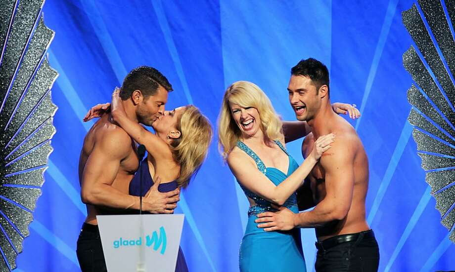 Jaymes Vaughan and James Davis, both presenters at the annual GLAAD media awards Saturday, May 11, 2013 in San Francisco, Calif get hugs and kisses from two unidentified women who won the honor after bidding in a take your shirt off auction. Photo: Lance Iversen, The Chronicle