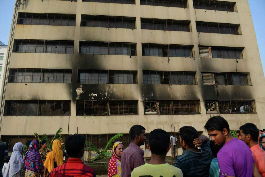 Workers stand outside an 11-story building that houses the Tung Hai Sweater Ltd. factory and apartments after a fire in Dhaka, Bangladesh, Thursday, May 9, 2013.  The fire broke out in the building Wednesday night, not long after the up to 300 workers of the factory went home for the day, killing at least eight people officials said Thursday. Photo: AP
