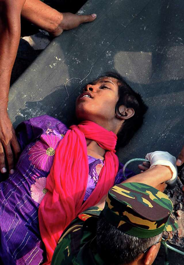 Survivor Reshma Begum lies on a stretcher after being pulled out from the rubble of a building that collapsed in Savar, near Dhaka, Bangladesh, Friday, May 10, 2013. Begum was working in a factory on the second floor of Rana Plaza when the building began collapsing around her April 24. She raced down a stairwell into the basement, where she became trapped near a Muslim prayer room in a wide space that allowed her to survive, she told the private Somoy TV. Photo: AP