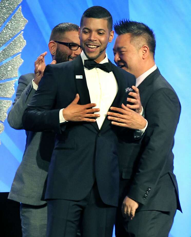 Guillermo Diaz, left rear, hugs Wilson Cruz on stage at the annual GLAAD media awards Saturday, May 11, 2013. Diaz and Rex Lee, right introduced Cruz who was the master of ceremonies in San Francisco, Calif. Photo: Lance Iversen, The Chronicle
