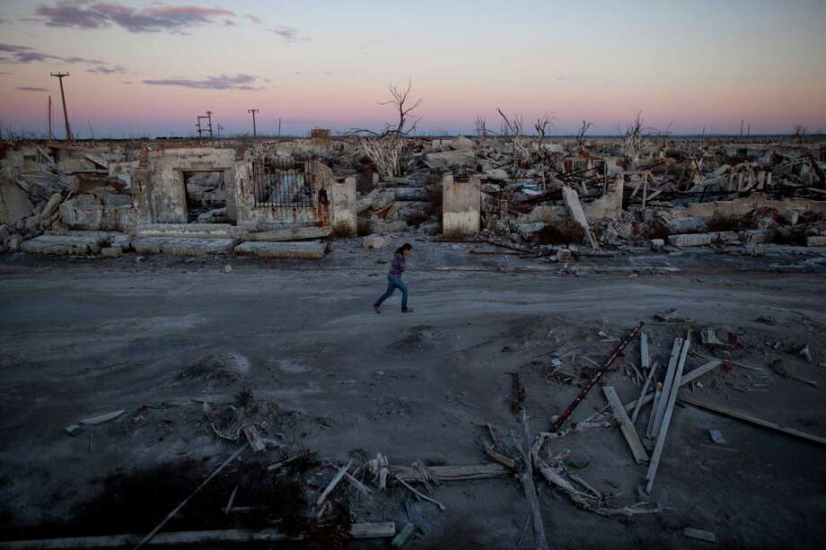 In this May 6, 2013 photo, former resident and tourist guide Norma Berg walks by a street in Epecuen, a village that once was submerged in water in Argentina. People come to see the rusted hulks of automobiles and furniture, crumbled homes and broken appliances. They climb staircases that lead nowhere, and wander through a graveyard where the water toppled headstones and exposed tombs to the elements. Photo: AP