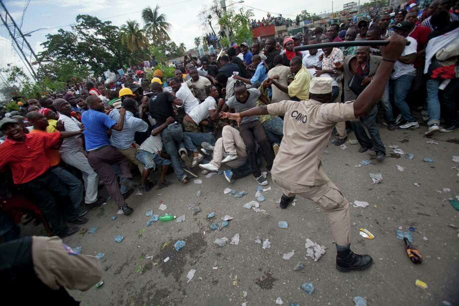 A police officer uses his baton to beat back supporters of Haiti's former president, Jean-Bertrand Aristide, after they gathered outside the courthouse where Aristide arrived earlier in the day in Port-au-Prince, Haiti, Wednesday, May 8, 2013. The two-time president showed up at the courthouse to testify before a judge investigating the 2000 slaying of Jean Dominique, one of the Caribbean country's most prominent journalists. Photo: AP