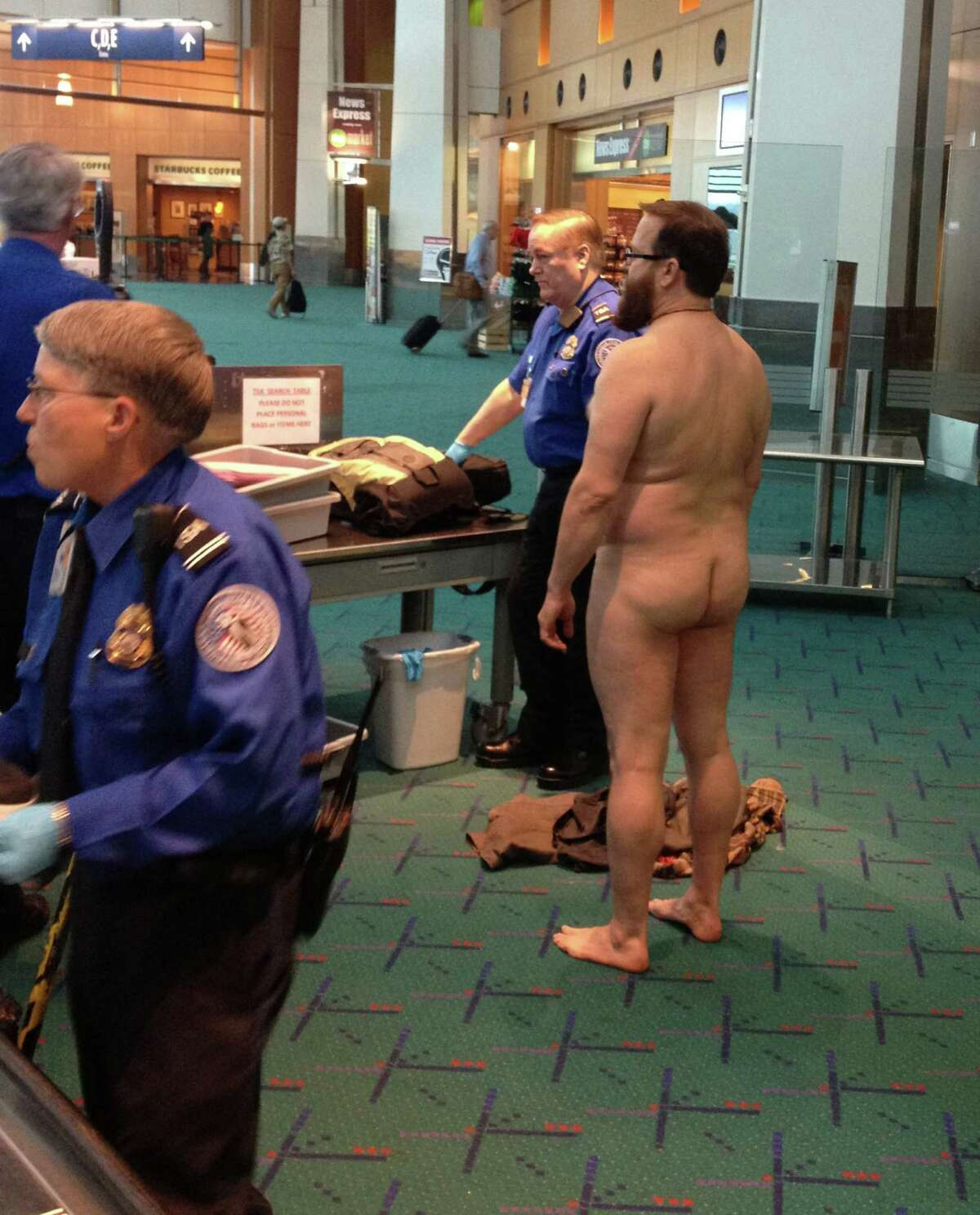 In this April 17, 2012, file photo, John E. Brennan stands naked after he stripped down while going through a security screening area at Portland International Airport, as a protest against airport security procedures. Brennan faces a $1,000 federal fine, an administrative hearing next week and he expects to lose. But he plans to press his free-speech argument into the federal courts. He says he wants more effective security checks that aren't so invasive. (AP Photo/Brian Reilly, File)