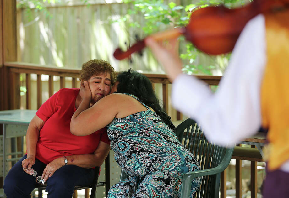 Mary Martinez, 74, left, gets a kiss from daughter-in-law Dora Martinez, 58, as they are serenaded by the all-female Mariachi Flor de Jalisco band for Mother's Day on Sunday. Photo: Jerry Lara, San Antonio Express-News / San Antonio Express-News