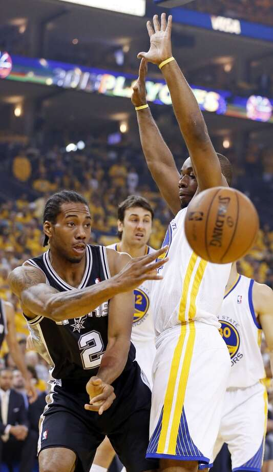 The Spurs' Kawhi Leonard passes around the Warriors' Carl Landry during first half action in Game 4 of the Western Conference semifinals Sunday, May 12, 2013 at Oracle Arena in Oakland.