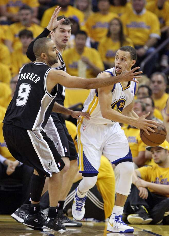 The Spurs' Tony Parker and Tiago Splitter defend the Warriors' Stephen Curry during first half action in Game 4 of the Western Conference semifinals Sunday May 12, 2013 at Oracle Arena in Oakland.