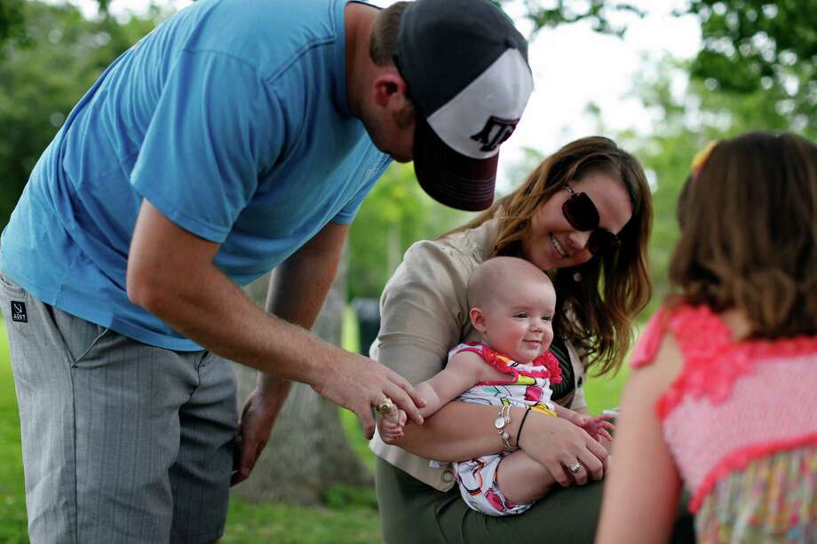 Taylor Fama, left, holds hands with his daughter, 4-month-old Mia Grace Fama, as her mother, Sarah Fama smiles and watches, Sunday, May 12, 2013 at Bay Area Park in Houston, Texas. The Famas along with other family members came to celebrate Mother's Day in the park. Photo: © TODD SPOTH, 2013 / © TODD SPOTH, 2013