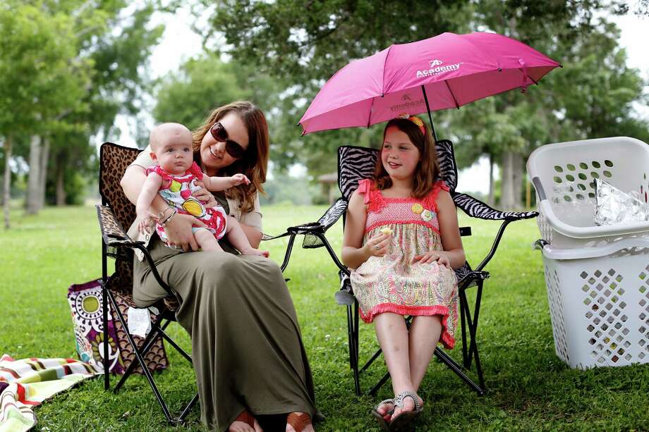 Sarah Fama, holds her 4-month-old daughter, Mia Grace, while her sister, 10-year-old Alexa, looks on, Sunday. Photo: © TODD SPOTH, 2013 / © TODD SPOTH, 2013