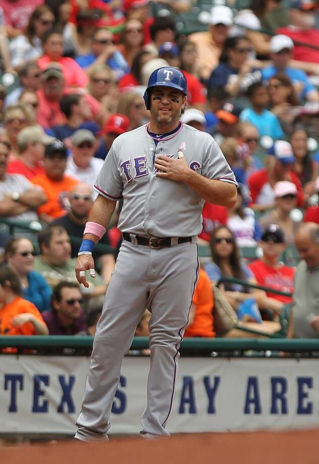 Lance Berkman of the Rangers makes a signal while at third base.