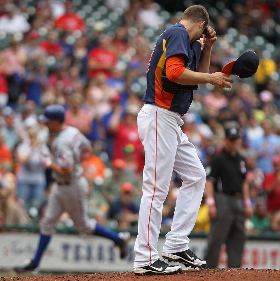 Astros pitcher Jordan Lyles wipes his face after allowing a home run to the Rangers.
