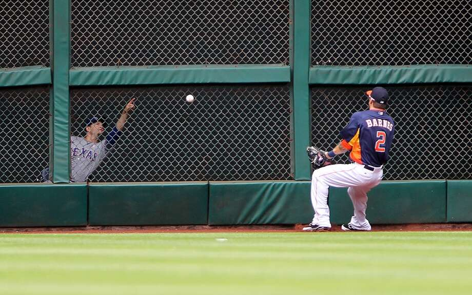 Astros outfielder Brandon Barnes tries to track down a ball hit off the wall by Lance Berkman of the Rangers.