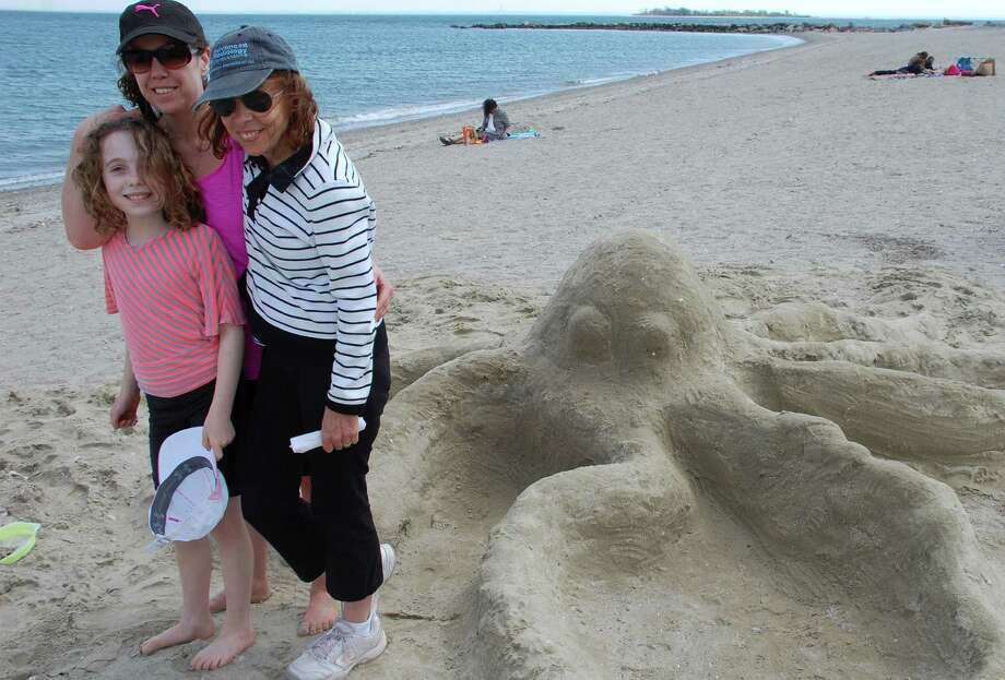 "Three generations of builders channeled their creativity into scuplting this octopus for the annual Castles in the Sand fundraiser for Homes with Hope at Compo Beach. On Sunday, Hannah Evan, 9, of Westport, her mother Michele Evan and grandmother Elaine Greenwald of Melville, N.Y., spent Mother's Day sculpting this sea monster named ""Ollie the Octopus.""  WESTPORT NEWS, CT 5/12/13 Photo: Jarret Liotta / Westport News contributed"