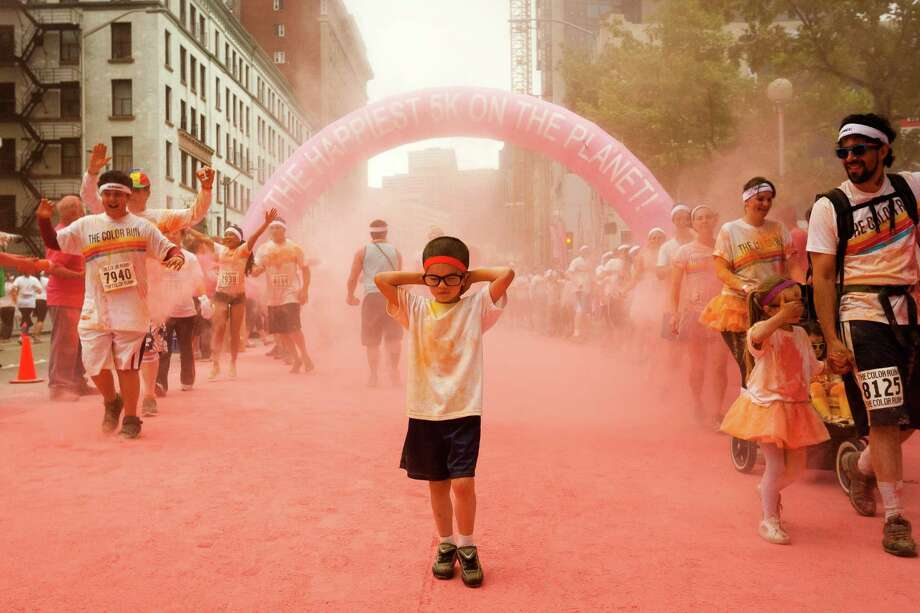 Runners pass through pink clouds of another powder station during the Color Run 5k Sunday, May 12, 2013, in Seattle. The sold out event - also known as the Happiest 5k on the Planet - is a unique paint race celebrating healthiness, happiness and individuality. Photo: JORDAN STEAD, SEATTLEPI.COM / SEATTLEPI.COM