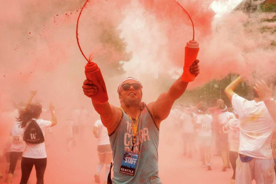 Race volunteers shoot pink clouds of powder at runners and into the air during the Color Run 5k Sunday, May 12, 2013, in Seattle. The sold out event - also known as the Happiest 5k on the Planet - is a unique paint race celebrating healthiness, happiness and individuality. Photo: JORDAN STEAD, SEATTLEPI.COM / SEATTLEPI.COM