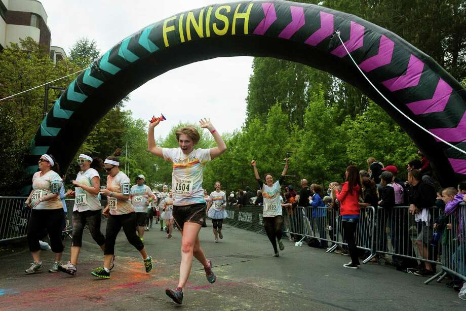 Participants cross the finish line of the Color Run 5k Sunday, May 12, 2013, in Seattle. The sold out event - also known as the Happiest 5k on the Planet - is a unique paint race celebrating healthiness, happiness and individuality. Photo: JORDAN STEAD, SEATTLEPI.COM / SEATTLEPI.COM
