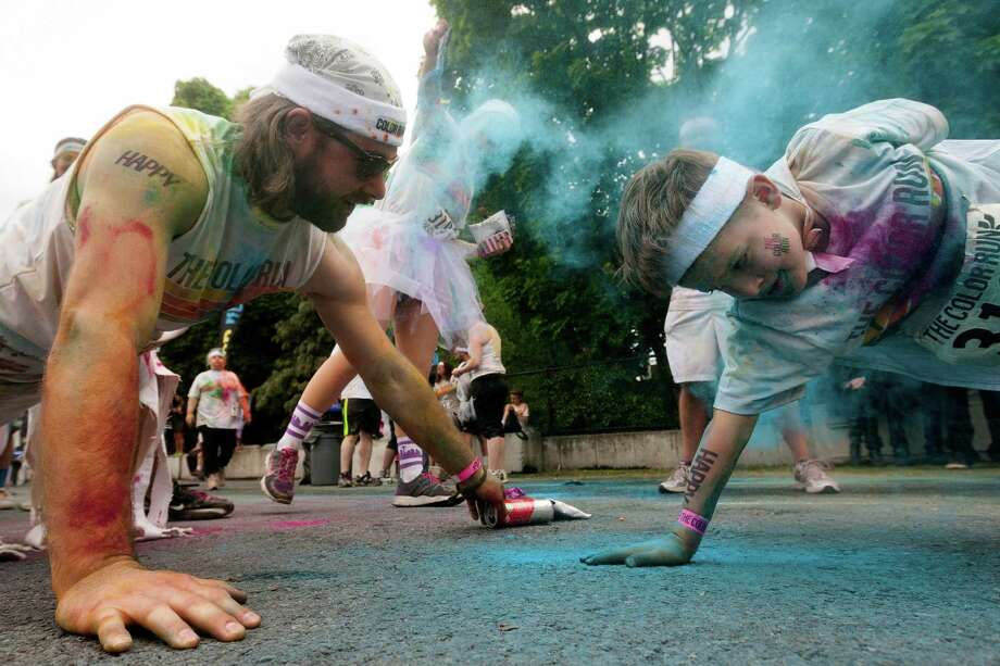 Attendees challenge each other to a push-up contest following the Color Run 5k Sunday, May 12, 2013, in Seattle. The sold out event - also known as the Happiest 5k on the Planet - is a unique paint race celebrating healthiness, happiness and individuality. Photo: JORDAN STEAD, SEATTLEPI.COM / SEATTLEPI.COM