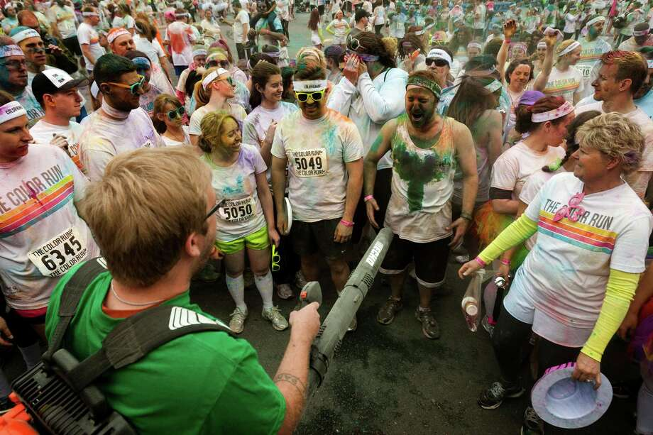 Following the completion of the running segment, participants gladly accepted the cleansing powers of a leaf blower to rid themselves of vibrant dust at the Color Run 5k Sunday, May 12, 2013, in Seattle. The sold out event - also known as the Happiest 5k on the Planet - is a unique paint race celebrating healthiness, happiness and individuality. Photo: JORDAN STEAD, SEATTLEPI.COM / SEATTLEPI.COM