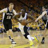 Golden State Warriors' Draymond Green, center, dribbles between San Antonio Spurs' Matt Bonner (15) and Manu Ginobili (20), of Argentina, during the first half of Game 4 of a Western Conference semifinal NBA basketball playoff series in Oakland, Calif., Sunday, May 12, 2013. (AP Photo/Marcio Jose Sanchez)
