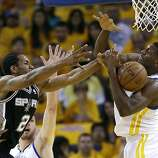 Golden State Warriors' Festus Ezeli, right, battles for a rebound against San Antonio Spurs' Kawhi Leonard (2) during the first half of Game 4 of a Western Conference semifinal NBA basketball playoff series in Oakland, Calif., Sunday, May 12, 2013. (AP Photo/Marcio Jose Sanchez)