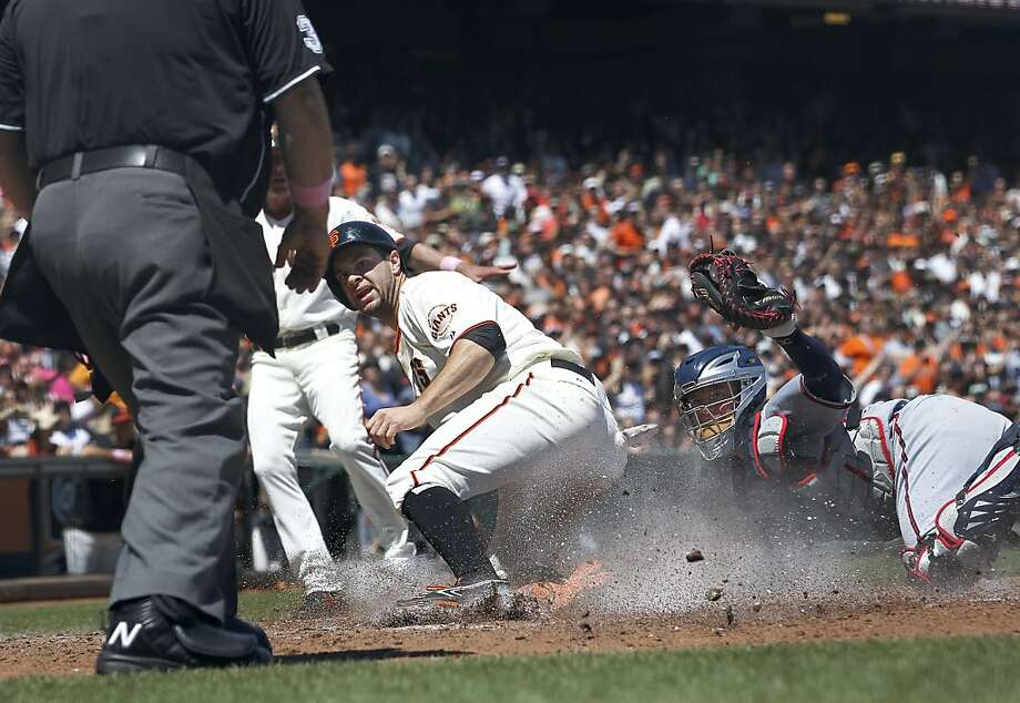 San Francisco Giants' Brandon Belt slides into homeplate safely past Atlanta Braves catcher Brian McCann (16) to score on a on a single by Brandon Crawford during the fourth inning of the National League MLB baseball game in San Francisco, Sunday, May 12, 2013. (AP Photo/Tony Avelar) Photo: Tony Avelar, Associated Press