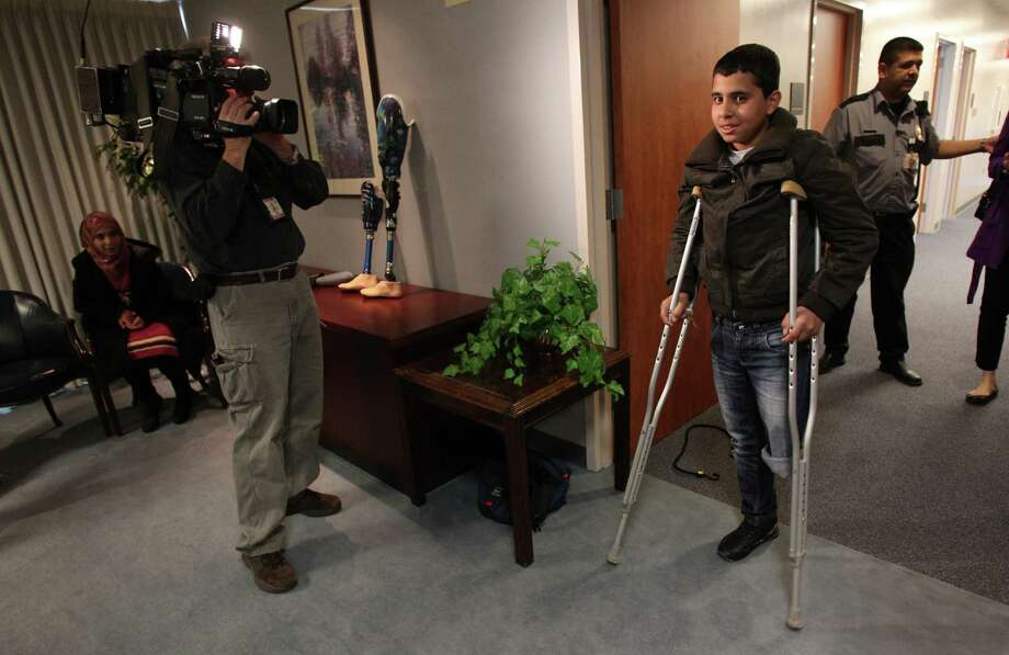 Mohammed Jammous, 14, of Syria, enters into the press conference where Fondren Orthopedic doctors will discuss his care at Texas Orthopedic Hospital on Thursday, Feb. 28, 2013, in Houston.  Mohammed Jammous was brought to Houston by The Palestinian Children's Relief Fund (PCRF), placed with host families since they are traveling without family. Photo: Mayra Beltran, Houston Chronicle / © 2013 Houston Chronicle
