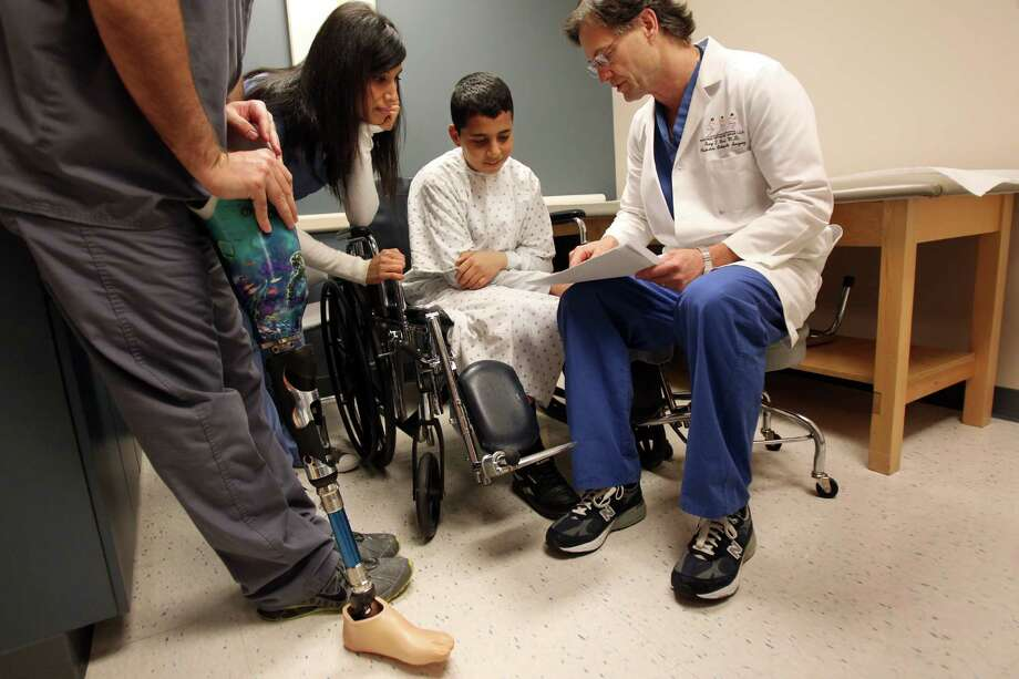 Translator Duha Ayish and Mohammed Jammous, 14, listen to Dr. Gary Brock, of Fondren Orthopedic Group, during his first medical consultation at Texas Orthopedic Hospital on Thursday, Feb. 28, 2013, in Houston. Mohammed Jammous will have minor stump revision surgery and a prosthesis.  Mohammed Jammous was brought to Houston from Syria by The Palestinian Children's Relief Fund (PCRF), and placed with host families since they are traveling without family. Photo: Mayra Beltran, Houston Chronicle / © 2013 Houston Chronicle