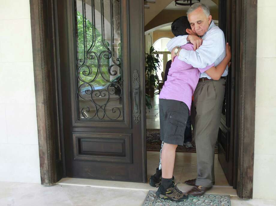 Mohammed Jamous, of Syria, hugs Bassam Barazi goodbye along with other members of his host family seconds before driving to IAH to start his long journey  home to Jordan on Wednesday, May 1, 2013, in Houston. Photo: Mayra Beltran / © 2013 Houston Chronicle