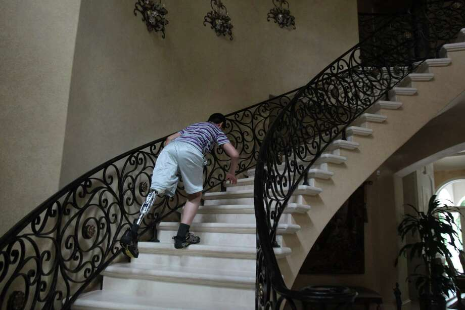 Mohammed Jamous, 15, ascends the stair case in the home of his host family after an hour of physical therapy on Thursday, March 28, 2013, in Houston.  The Palestine Children's Fund Houston Chapter has helped Mohammed Jamous, of Syria, travel to the U.S. from Jordan on a medical visa without his family to receive a custom prosthetic leg. Photo: Mayra Beltran, Houston Chronicle / © 2013 Houston Chronicle