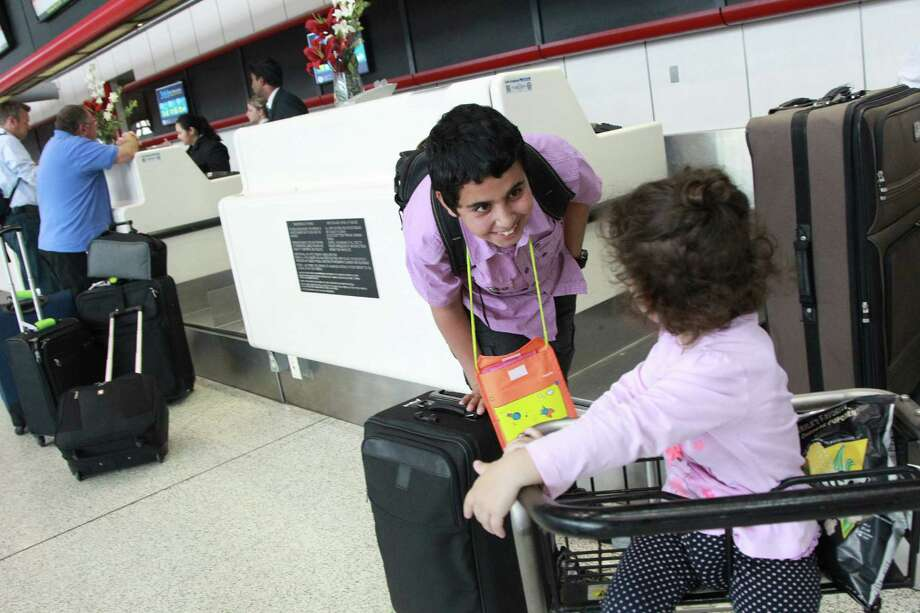Mohammed Jamous, of Syria, plays with Tala Khayyal at IAH while Rania Awwad, of The Palestinian Children's Relief Fund, escorts him to the gate to start his long journey home to Jordan on Wednesday, May 1, 2013, in Houston. Photo: Mayra Beltran / © 2013 Houston Chronicle