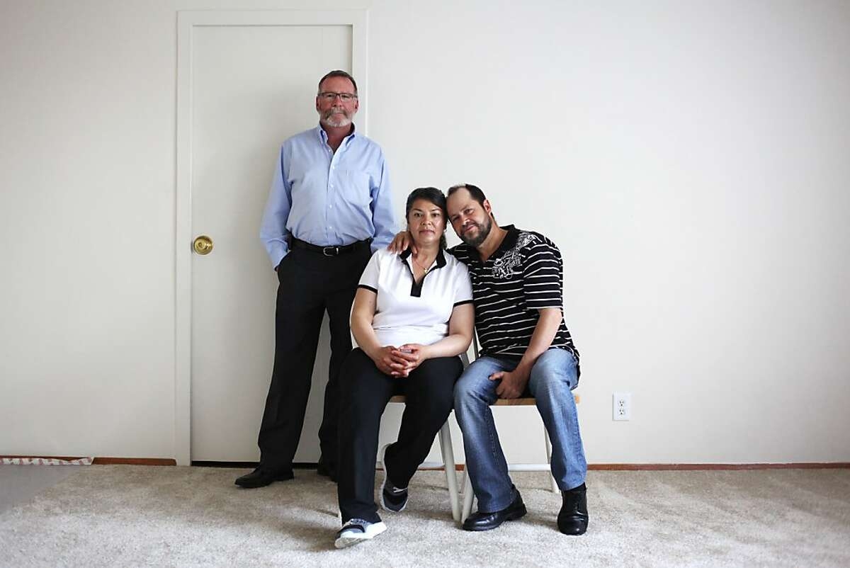 Francisco and Marta Agredano (seated) pose for a portrait with Benjamin Amyes, an emergency response coordinator with HSA, on May 2, 2013 in San Francisco, Calif. The Agredanos are living in Parkmerced under San Francisco's Good Samaritan Tenancy after being displaced from their Capp Street home in a December fire. The family lost most of their possessions in the fire, including all of their furniture and appliances.