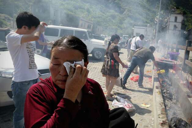 A mother cries for her son at the ruins of earthquake-hit Beichuan county during the five year anniversary of the Wenchuan Earthquake on May 12, 2013 in Mianyang, China. Many commemoration activities will be held to mark the fifth anniversary of the devastating earthquake that struck Sichuan Province on May 12, 2008 and claimed nearly 90,000 lives. Photo: Feng Li, Getty Images / 2013 Getty Images