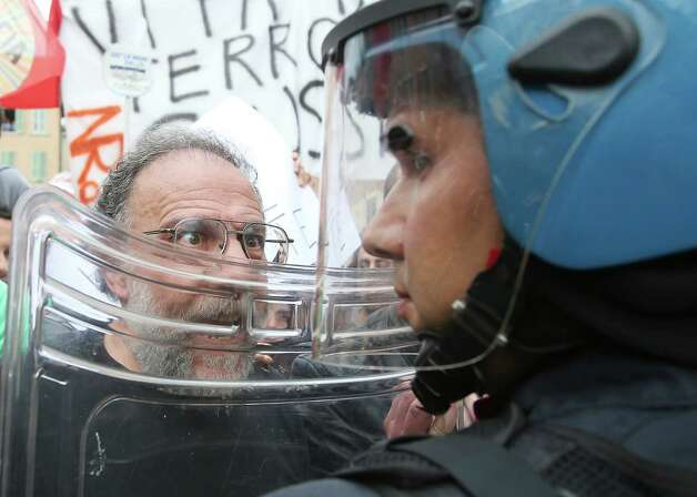 "A man faces Police as Silvio Berlusconi delivers his speech in Brescia, Italy, Saturday, May 11, 2013. Thousands of supporters of former Premier Silvio Berlusconi rallied in a northern Italian city Saturday to protest the media mogul's recent conviction by a Milan appeals court for tax fraud, cheering their hero as police in riot gear separated them from jeering opponents. The backers turned out for the ""Everyone for Silvio"" rally in a square outside the cathedral in Brescia, a small industrial city that is a bastion of the conservative leader's political support. As some arrived, waving pro-Berlusconi banners, some detractors shouted ""jail, jail."" Helmeted police holding plastic body shields moved in between the noisy camps to prevent any physical violence. Photo: Antonio Calanni, Associated Press / AP"