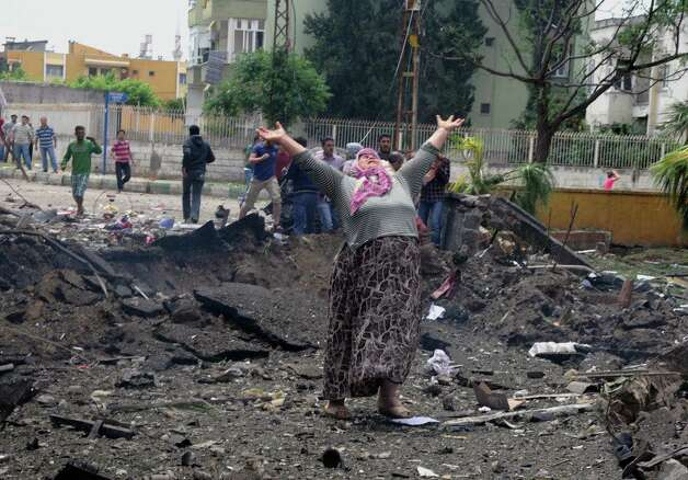 A woman cries at the scene of one of the explosion sites, after several explosions killed at least 18 people and injured dozens in Reyhanli, near Turkey's border with Syria, Saturday, May 11, 2013, Turkish Interior Minister Muammer Guler said. Photo: Cem Genco, Associated Press / Anadolu Agency
