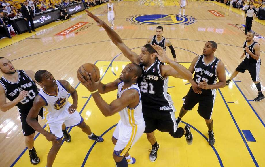 The Warriors' Carl Landry looks for room around the Spurs' Tim Duncan as the Spurs' Manu Ginobili, Warriors' Harrison Barnes,  and Spurs' Boris Diaw look on in Game 4 of the Western Conference semifinals Sunday, May 12, 2013 at Oracle Arena in Oakland. The Warriors won 97-87 in overtime.