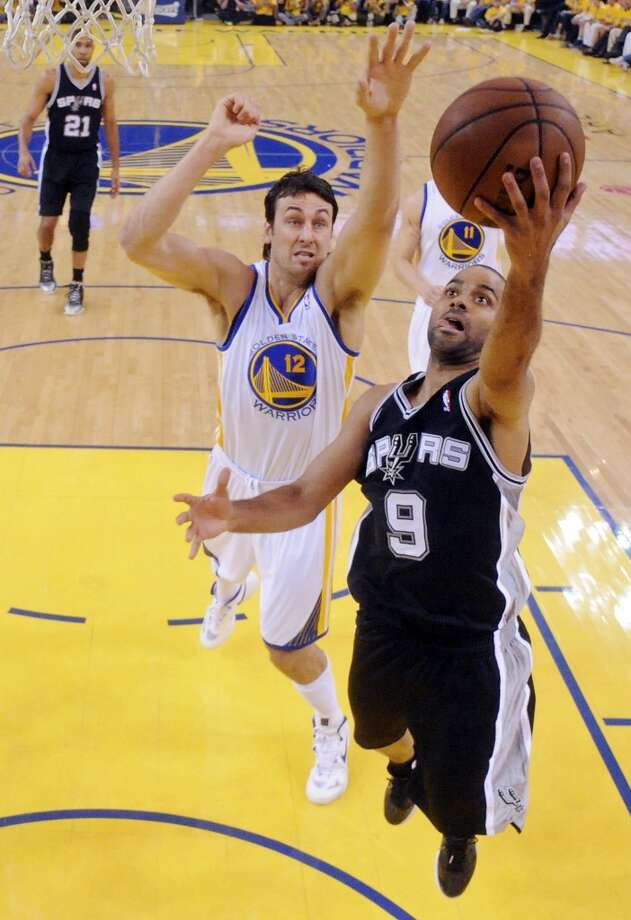 The Spurs' Tony Parker shoots around the Warriors' Andrew Bogut in Game 4 of the Western Conference semifinals Sunday, May 12, 2013 at Oracle Arena in Oakland. The Warriors won 97-87 in overtime.