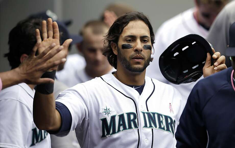 Seattle Mariners' Michael Morse is congratulated after scoring against the Oakland Athletics in the fourth inning of a baseball game on Sunday, May 12, 2013, in Seattle. (AP Photo/Elaine Thompson) Photo: Elaine Thompson, Associated Press