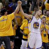 Stephen Curry (30) of the Warriors got a high five from a fan after two points late in the second half. The Golden State Warriors beat the San Antonio Spurs 97-87 in the playoffs Sunday May 12, 2013 at Oracle Arena in Oakland, Calif.