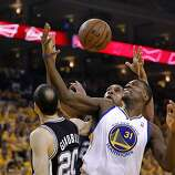 The Warriors Festus Ezeli (31) did battle for a rebound with Manu Ginobli (20) and Tim Duncan. The Golden State Warriors beat the San Antonio Spurs 97-87 in the playoffs Sunday May 12, 2013 at Oracle Arena in Oakland, Calif.