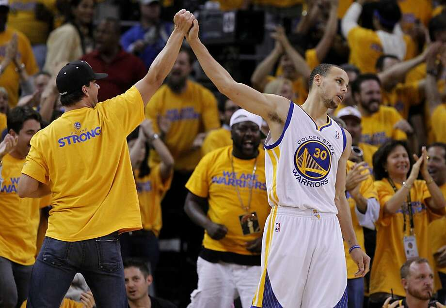 Stephen Curry (30) got a high five from a fan on the sidelines after an important two points late in the second half. The Golden State Warriors beat the San Antonio Spurs 97-87 in the playoffs Sunday May 12, 2013 at Oracle Arena in Oakland, Calif. Photo: Brant Ward, The Chronicle