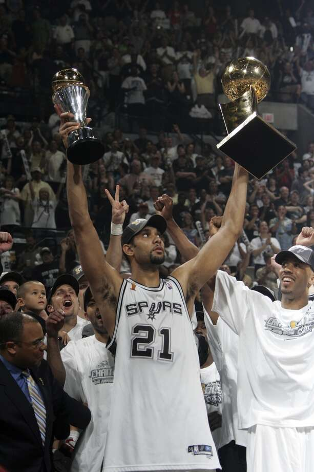 ... and the NBA Championship.PHOTO: The Spurs' Tim Duncan holds up the MVP and NBA Championship trophies during the post-game celebration after the Spurs beat the Pistons in Game 7 of the NBA Finals at the SBC Center on June 23, 2005. Photo: Kin Man Hui, San Antonio Express-News