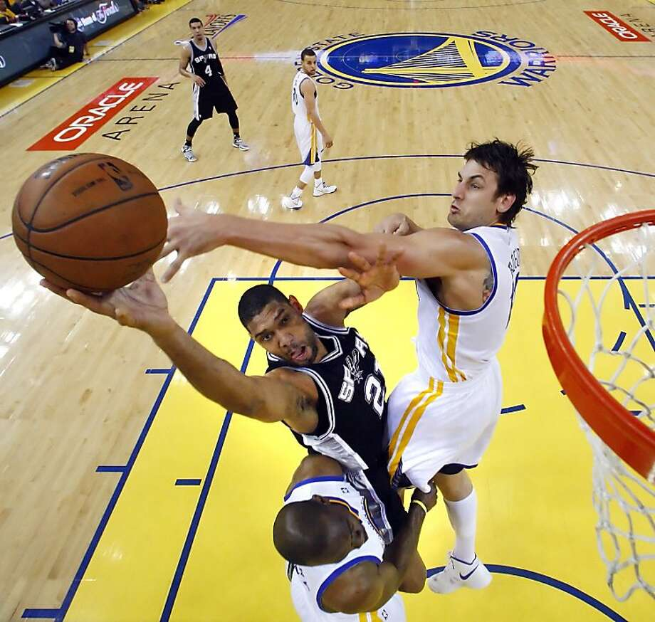 Andrew Bogut (12) defends against a shot by Tim Duncan (21) in the first half. The Golden State Warriors played the San Antonio Spurs in Game 4 of the Wester Conference Semifinals at Oracle Arena in Oakland, Calif., on Sunday, May 12, 2013. Photo: Carlos Avila Gonzalez, The Chronicle
