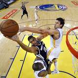 Andrew Bogut (12) defends against a shot by Tim Duncan (21) in the first half. The Golden State Warriors played the San Antonio Spurs in Game 4 of the Wester Conference Semifinals at Oracle Arena in Oakland, Calif., on Sunday, May 12, 2013.